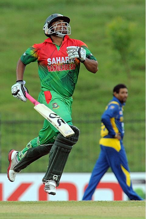 Bangladeshi cricketerTamim Iqbal (L) celebrates his century (100 runs) during the opening one-day international (ODI) match between Sri Lanka and Bangladesh at The Suriyawewa Mahinda Rajapakse Interna