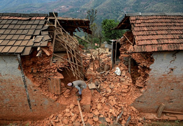 A resident tries to clear debris of his house at a village following Saturday's earthquake in Nepal. (Reuters)