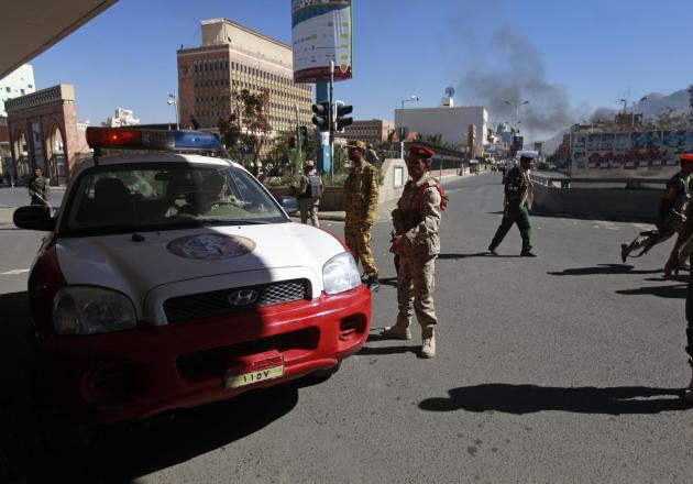 A police car blocks a road leading to the Defense Ministry's compound as smoke rises after an attack, in Sanaa