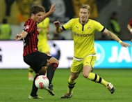 Dortmund's striker Marco Reus (R) and Frankfurt's Swiss midfielder Pirmin Schwegler fight for the ball during their German first division Bundesliga football match in Frankfurt am Main, central Germany. The match ended in a 3-3 draw