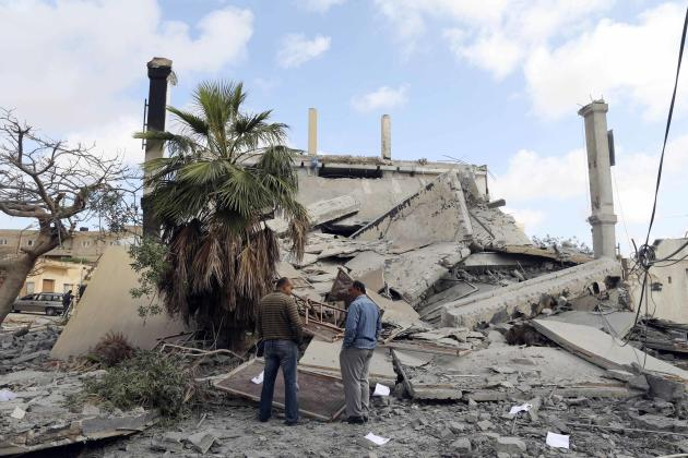 Two men stand in front of the wreckage of a building that was destroyed yesterday in Benghazi
