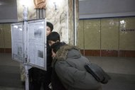 In this March 10, 2011 photo, men read a newspaper on public display inside a subway station in Pyongyang, North Korea. (AP Photo/David Guttenfelder)