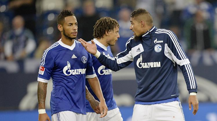 Schalke's Kevin-Prince Boateng of Ghana, right, talks to Dennis Aogo, left, after losing the German soccer Bundesliga match between FC Schalke 04 and Bayern Munich at the arena in Gelsenkirchen, Germany, Saturday, Sept. 21, 2013. Schalke was defeated by Bayern with 0-4