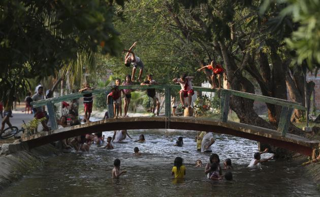 Children play in an irrigation canal, the local swimming hole that runs though Aracataca, the hometown of the late Nobel laureate Gabriel Garcia Marquez along Colombia's Caribbean coast during the
