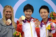 China's Ye Shiwen (C) holds her gold medal next to silver medallist US swimmer Elizabeth Beisel (L) and bronze medallist China's Li Xuanxu on the podium of the women's 400m individual medley final swimming event at the London 2012 Olympic Games
