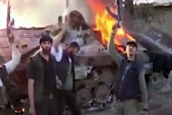 An image grab taken from a video uploaded on YouTube allegedly shows Syrian rebels raising their guns next to a burning tank after their confrontation with Syrian Army on the outskirts of Duma