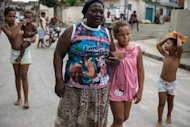 "Denaide Alves da Fonseca wears a shirt of her carnival drum group ""Batuqueiros do Mandela"" at Mandela shantytown (favela) in Rio de Janeiro, Brazil, on December 6, 2013"