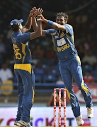 Sri Lankan cricket team captain Angelo Mathews (R) celebrates with teammate Shaminda Eranga after dismissing West Indies batsman Darren Bravo during the fifth match of the Tri-Nation series between Sri Lanka and West Indies at the Queen's Park Oval stadium in Port of Spain on July 8, 2013