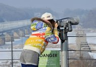 "A visitor looks at North Korea through binoculars at Imjingak in Paju near the demilitarized zone dividing the two Koreas on February 13, 2013. ""The prospect that the North will sell highly-enriched uranium, nuclear weapons designs or even nuclear weapons to all comers, is not a happy thought if you live in one of America's cities,"" Robert Gallucci, president of the MacArthur Foundation, said"