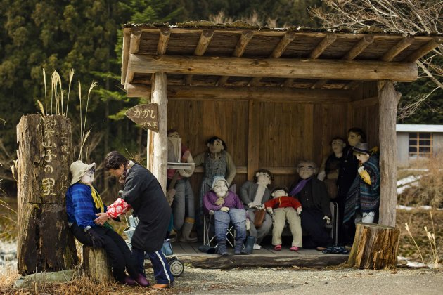 Tsukimi Ayano arranges a scarecrow at a bus stop in the mountain village of Nagoro. (Reuters)