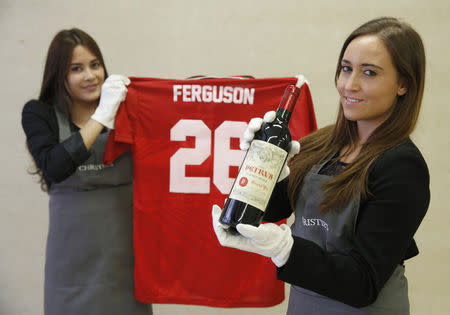 "Employees pose with a bottle of ""Petrus 1988"" wine and a Manchester United Champions League shirt signed by Ferguson, at Christie's auction house in London"