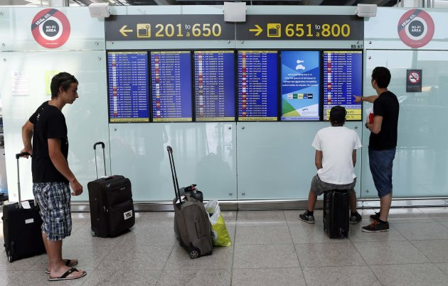 People look at boards displaying flight information in Barcelona's airport, August 8, 2014. (Reuters)