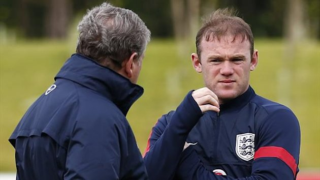 England manager Roy Hodgson (L) speaks to Wayne Rooney during a training session