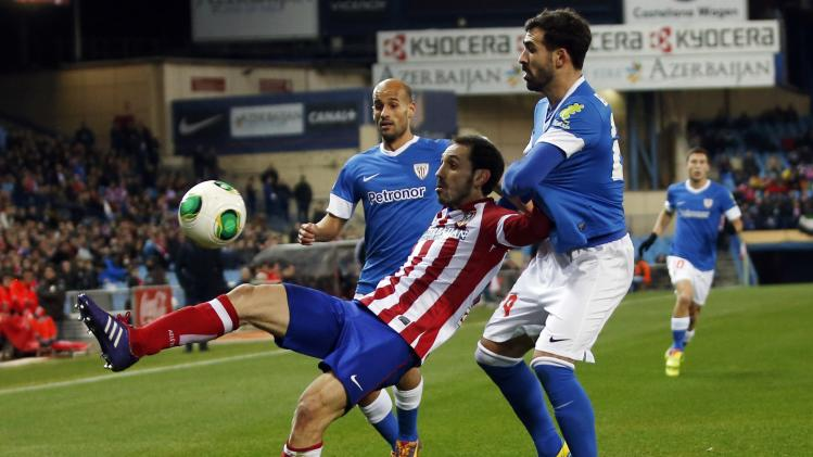 Atletico Madrid's Torres and Athletic Bilbao's Balenziaga fight for the ball during their Spanish King's Cup quarter-final first leg soccer match in Madrid