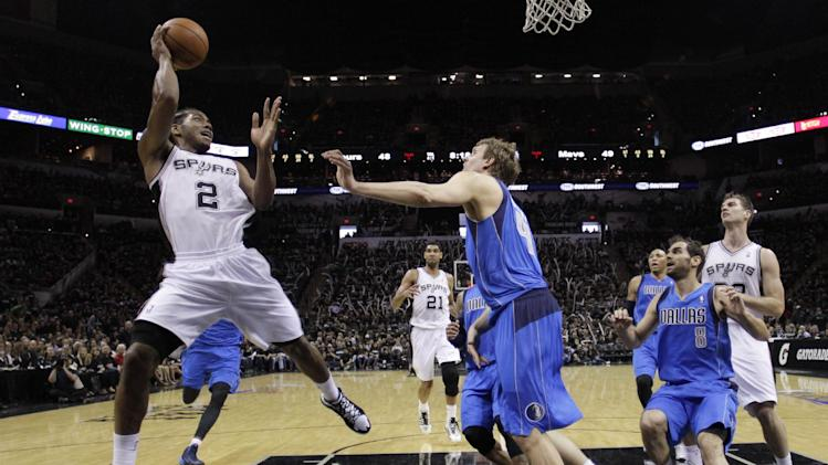 San Antonio Spurs' Kawhi Leonard (2) makes an off-balance shot over Dallas Mavericks' Dirk Nowitzki (41), of Germany, during the second half of Game 1 of the opening-round NBA basketball playoff series on Sunday, April 20, 2014, in San Antonio. San Antonio won 90-85