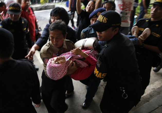 "Government security officials carry a family member of passengers onboard AirAsia flight QZ8501 after she collapsed at a waiting area in Juanda International Airport, Surabaya, December 30, 2014. Indonesian rescuers saw bodies and luggage off the coast of Borneo island on Tuesday and officials said they were ""95 percent sure"" debris spotted in the sea was from a missing AirAsia plane with 162 people on board. Indonesia AirAsia's Flight QZ8501, an Airbus A320-200, lost contact with air traffic control early on Sunday during bad weather on a flight from the Indonesian city of Surabaya to Singapore. REUTERS/Beawiharta (INDONESIA - Tags: DISASTER ENVIRONMENT TPX IMAGES OF THE DAY)"