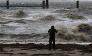 A man takes pictures of the North Sea near the town of Emden, December 6, 2013. REUTERS/Ina Fassbender