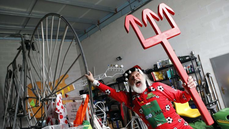 "German bicycle designer Didi Senft, also known as ""El Diablo"", poses with his trident after presenting his new bicycle creation to commemorate the 2014 FIFA World Cup, in the town of Storkow"