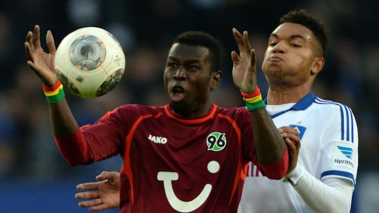 Hamburg's JonathanTah, right,  vies for the ball with Hannover's Mame Diouf during the German Bundesliga soccer match between Hamburger SV and Hannover 96 at Imtech Arena in Hamburg,Germany, Sunday Nov. 24, 2013
