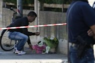 A man places flowers on the site of a blast near a school in Brindisi. Italy was in shock on Saturday after an unexplained bombing at a school killed a 16-year-old girl and left five other teens gravely injured, sparking emotional protests across the country