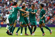 Mexico's midfielder Javier Aquino (11) celebrates with teammates after scoring a goal against Senegal in the quarterfinal of Men's football match between Mexico and Senegal at Wembley Stadium in London, on August 4, 2012 during the London 2012 Olympic Games. AFP PHOTO / KHALED DESOUKI