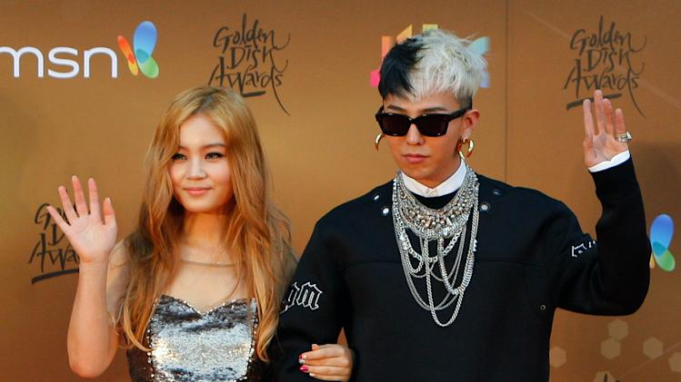 South Korean singers Lee Hi, left, and G-Dragon pose for photographers as they arrive on the red carpet ahead of the 27th Golden Disk Awards at Sepang International Circuit in Sepang, Malaysia, Wednesday, Jan. 16, 2013. (AP Photo/Lai Seng Sin)