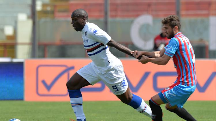 Sampdoria forward Stefano Okaka, left, challenges for the ball with Catania defender Gino Peruzzi, of Argentina, during their Serie A soccer match at the Angelo Massimino stadium in Catania, Italy, Saturday, April 19, 2014