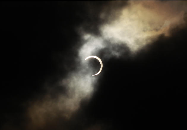 An annular solar eclipse is seen briefly during a break in clouds over Taipei, Taiwan, Monday, May 21, 2012. The annular solar eclipse, in which the moon passes in front of the sun leaving only a gold