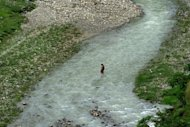 Photo illustration shows a woman crossing a river in Pokhara, near Kathmandu, during monsoon season. At least 14 pilgrims were killed when a jeep carrying them to a sacred Hindu site in southern Nepal swerved off a highway and fell 100 metres into a stream below, police said on Saturday