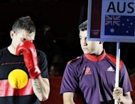 Damien Hooper (L) of Australia is dressed in a T-shirt bearing the Aboriginal colours as he arrives for his first round Light-heavyweight (81kg) match of the London 2012 Olympic Games against Marcus Browne of the USA at the Excel Arena in London. Hooper, who went on to win a 13-11 points decision, could face some form of sanction for wearing the Aboriginal colours