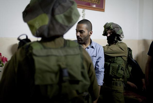In this photo taken April 17, 2014 released by the Warren Film, American director James Adolphus directs actors dressed in Israeli army uniforms at the filming location of his movie in the West Bank c