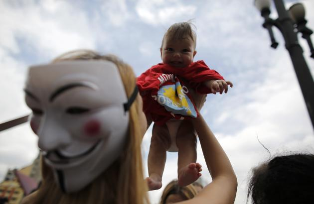 Woman, wearing a Guy Fawkes mask, holds up a homeless child during a Christmas street celebration in downtown Sao Paulo