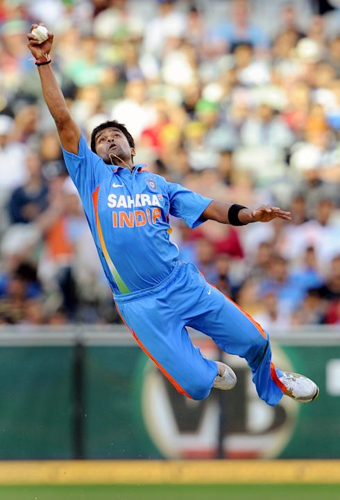 Indian paceman Vinay Kumar leaps high to field the ball off his own bowling from the Australian batsman in their international one day cricket match at the Melbourne Cricket Ground (MCG), on February