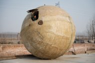 This photo taken on December 11, 2012 shows farmer Liu Qiyuan looking out from a survival pod that he built, in the village of Qiantun, south of Beijing. Liu's seven completed or under-construction pods, made using a fibreglass casing over a steel frame, have cost him 300,000 yuan ($48,000) each, he says, and are equipped with oxygen tanks, food and water supplies