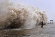 A man running away from a huge wave pushed up by Typhoon Usagi on a wharf in Shantou, south China's Guangdong province on September 22, 2013