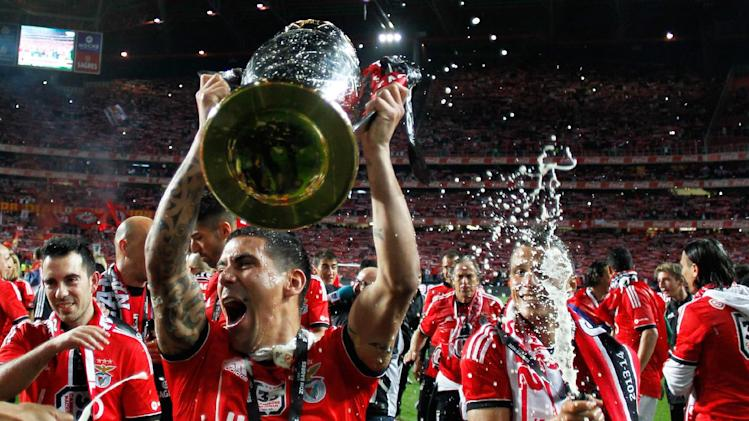 Benfica's Maxi Pereira, from Uruguay, lifts the trophy while teammate Lima, from Brazil, sprays sparkling wine celebrating at the end of their Portuguese league soccer match with Olhanense on Sunday April 20, 2014, at Benfica's Luz stadium in Lisbon. Benfica defeated Olhanense 2-0 to win the championship with two rounds left to play