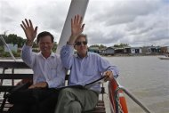 U.S. Secretary of State John Kerry and Dr. Dang Kieu Nhan (L) wave goodbye after Kerry spoke in Tan An Tay along the Mekong River Delta December 15, 2013. REUTERS/Brian Snyder