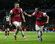 Arsenal's Santi Cazorla (R) runs to congratulate Lukas Podolski as he celebrates scoring their second goal against Olympiakos FC during the UEFA Champions League Group B match at the Emirates Stadium in London. Arsenal won 3-1