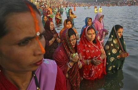 Hindu devotees stand in the waters of Sun Lake to offer prayers to the Sun god during the Hindu religious festival Chhat Puja in Chandigarh