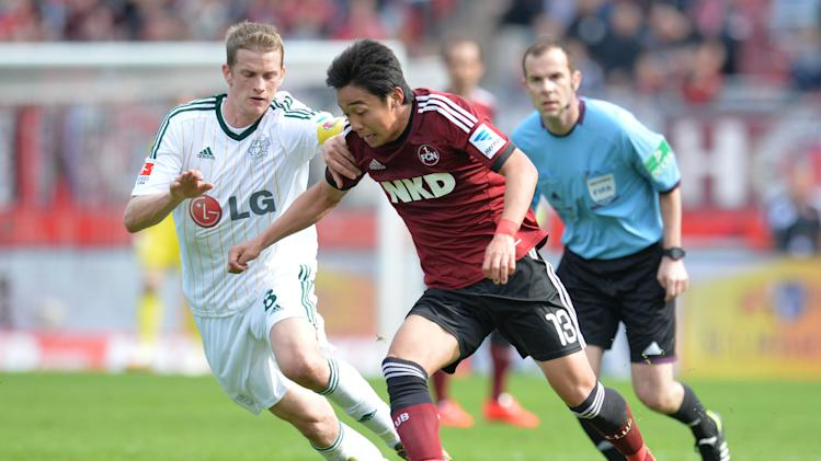 Nuremberg's Hiroshi Kiyotake, right,and Leverkusen's Lars Bender vie for the ball during the German Bundesliga soccer match between 1. FC Nuremberg and Bayer 04 Leverkusen at Grundig-Stadion in Nuremberg, Germany, April 20, 2014