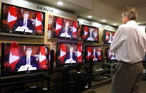 An electronics store employee watches Canada's Prime Minister Stephen Harper deliver a national televised address in Calgary