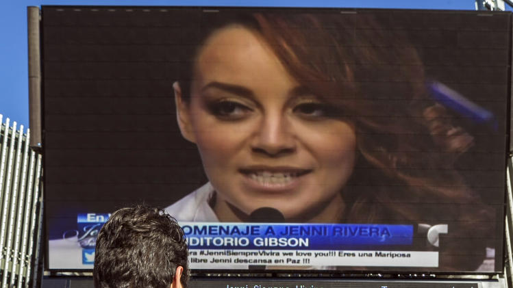 Fans of the late singer Jenni Rivera watch a live broadcast of her memorial service Wednesday, Dec. 19, 2012 at Universal City in Los Angeles. Rivera, a Mexican-American singer and reality TV star, was killed in a Dec. 9 plane crash. (AP Photo/Damian Dovarganes)