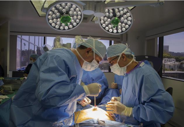 Doctors make an incision in the belly button of Sheryl, who had two fibroids, in preparation for a single-site robotic-assisted hysterectomy at miVIP Surgery Center, in Los Angeles, California