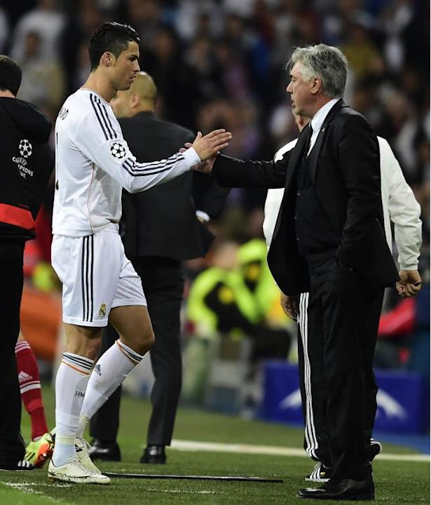 Real Madrid forward Cristiano Ronaldo (L) leaves the pitch congratulated by Italian coach Carlo Ancelotti during the UEFA Champions League semifinal first leg football match Real Madrid CF vs FC Bayer