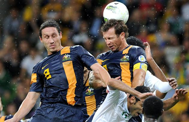 Australia's Lucas Neill (R) And Mark Mulligan (R) Rise Above The Saudi Arabian Counterparts AFP/Getty Images