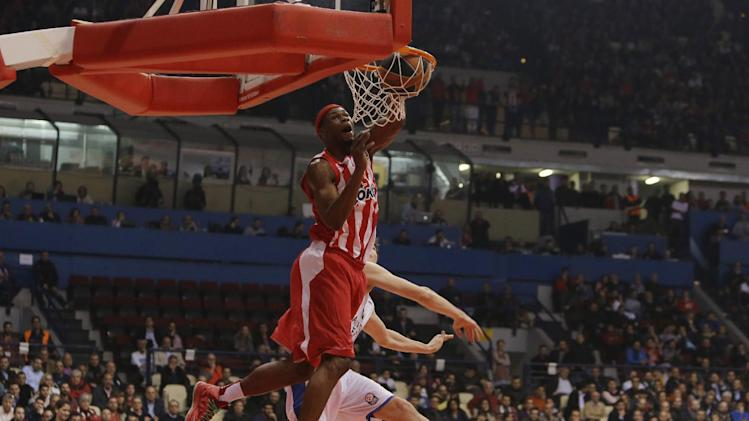 Olympiakos' Brent Petway dunks a ball past Anadolou Efes' Cedi Osman during their Euroleague basketball match of Top 16 in the port of Piraeus, near Athens, Greece, Thursday, Feb. 13, 2014