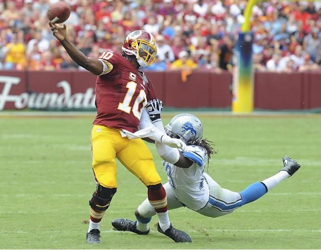 Washington Redskins quarterback Robert Griffin III is pulled to the turf by Detroit Lions defensive end Willie Young during the first half of a NFL football game in Landover, Md., Sunday, Sept. 22, 20