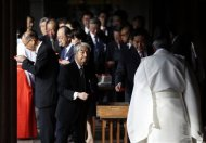 A group of lawmakers including Japan's ruling Liberal Democratic Party (LDP) lawmaker Hidehisa Otsuji (C) and former land minister Yuichiro Hata (3rd R), walk after paying their respects to the war dead at Yasukuni Shrine in Tokyo October 18, 2013. REUTERS/Toru Hanai