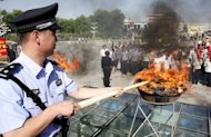 A Chinese policeman lits a cauldron filled with illicit drugs during a 2009 ceremony in Hami, Xinjiang region. China has executed four convicted drug traffickers and sentenced at least 15 others to death as the nation marked global anti-drug day