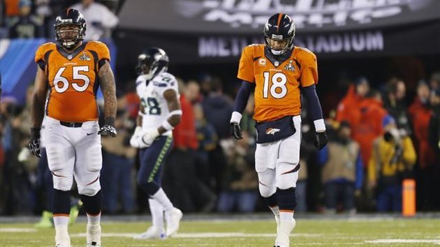 Denver Broncos quarterback Peyton Manning (18) walks with teammate Louis Vasquez after a play against the Seattle Seahawks during the second quarter in the NFL Super Bowl XLVIII football game